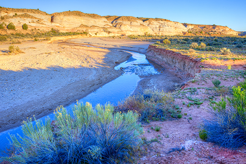 Paria River flowing through the base of the Vermillion Cliffs in desert landscape of Arizona.